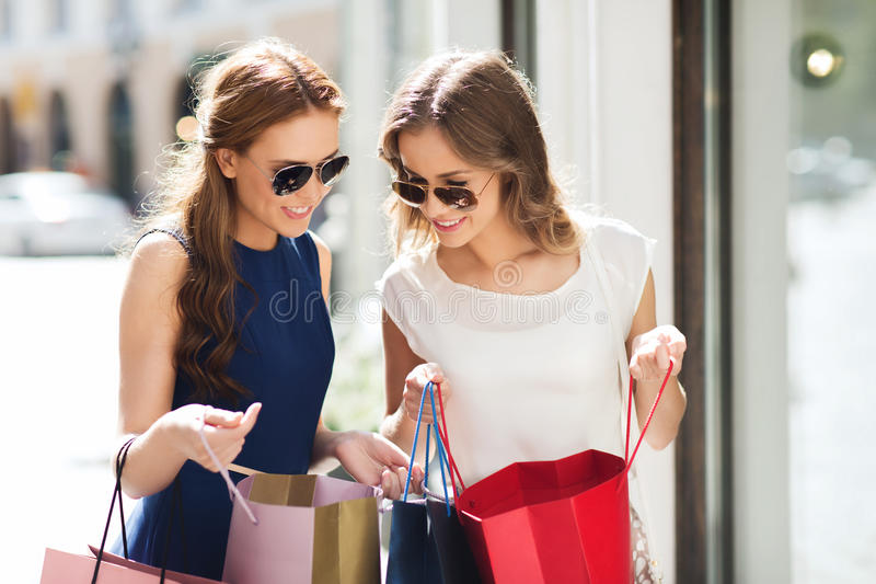 Happy women with shopping bags in city. Sale, consumerism and people concept - happy young women looking into shopping bags at shop window in city royalty free stock photography