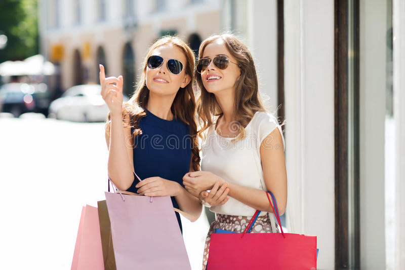 Happy women with shopping bags in city. Sale, consumerism and people concept - happy young women with shopping bags pointing finger in city stock photography