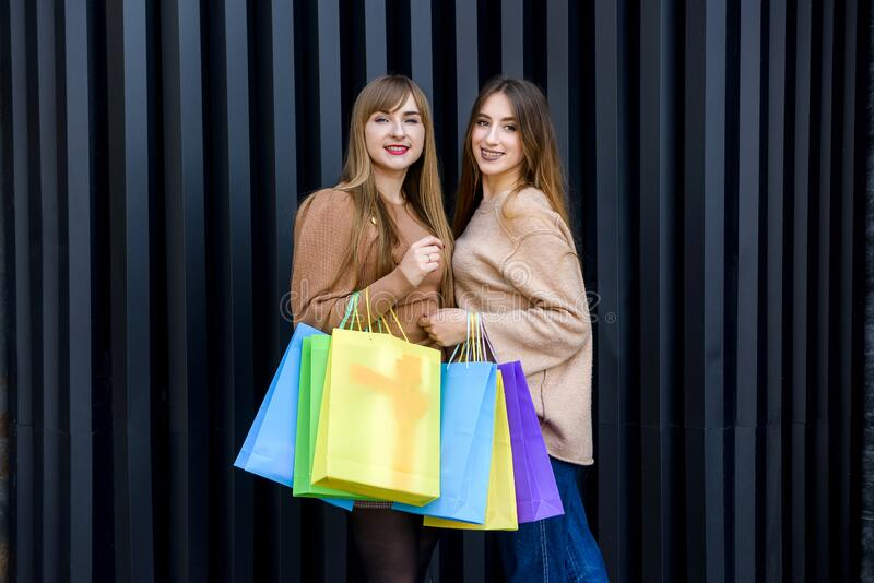 Happy women with shopping bags in fur coats posing on city street.  royalty free stock photo