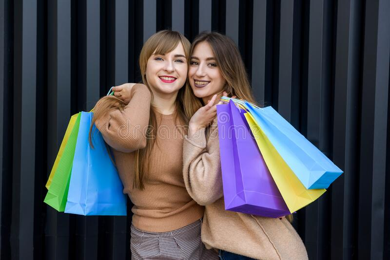 Happy women with shopping bags in fur coats posing on city street.  stock image