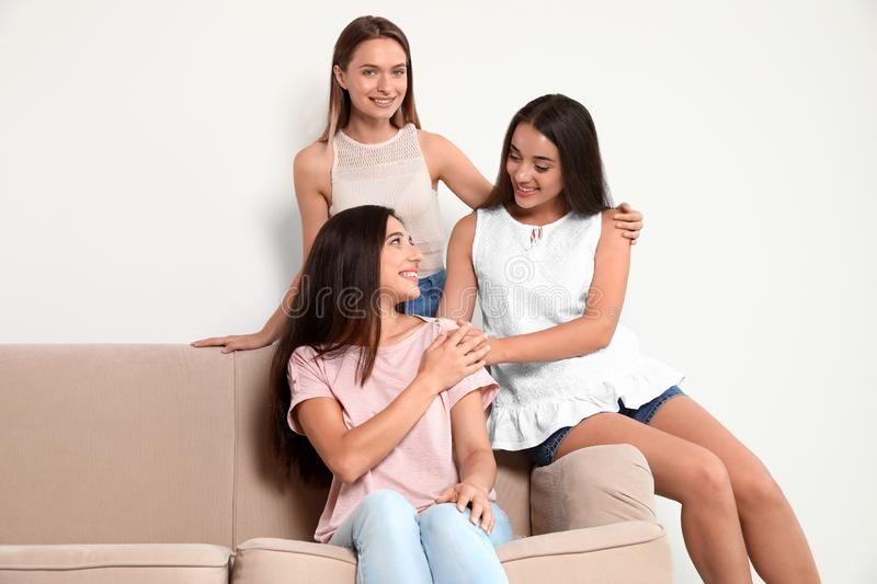 Happy women sitting on sofa near wall. Girl power concept stock images