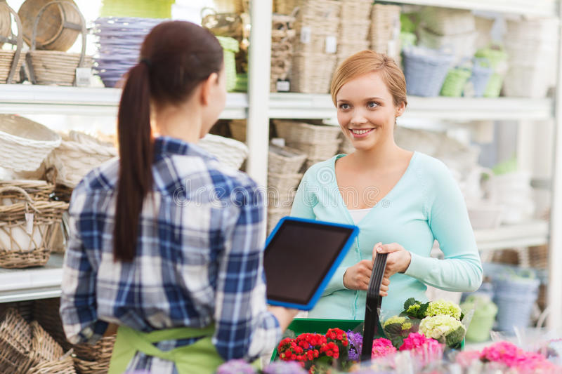 Happy women with tablet pc at flower shop. People, gardening, shopping, sale and consumerism concept - happy gardener with tablet pc helping women with choosing royalty free stock image