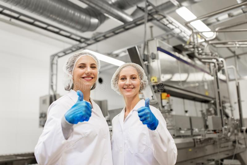 Happy women technologists at ice cream factory royalty free stock photography