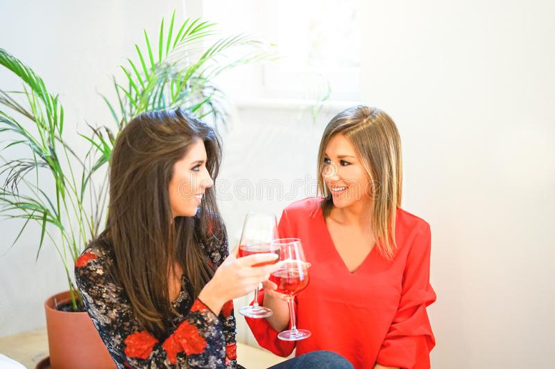 Happy women toasting and cheering glasses of red wine in apartment - Young friends having fun drinking at home. Frienship, drinks, lifestyle concept stock images