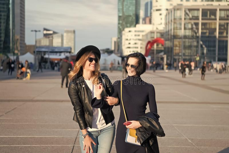 Happy women walk in business district of La Defense, Paris. Girls smile in fashionable clothes on sunny day on urban environment. Vacation, travel, wanderlust royalty free stock photography
