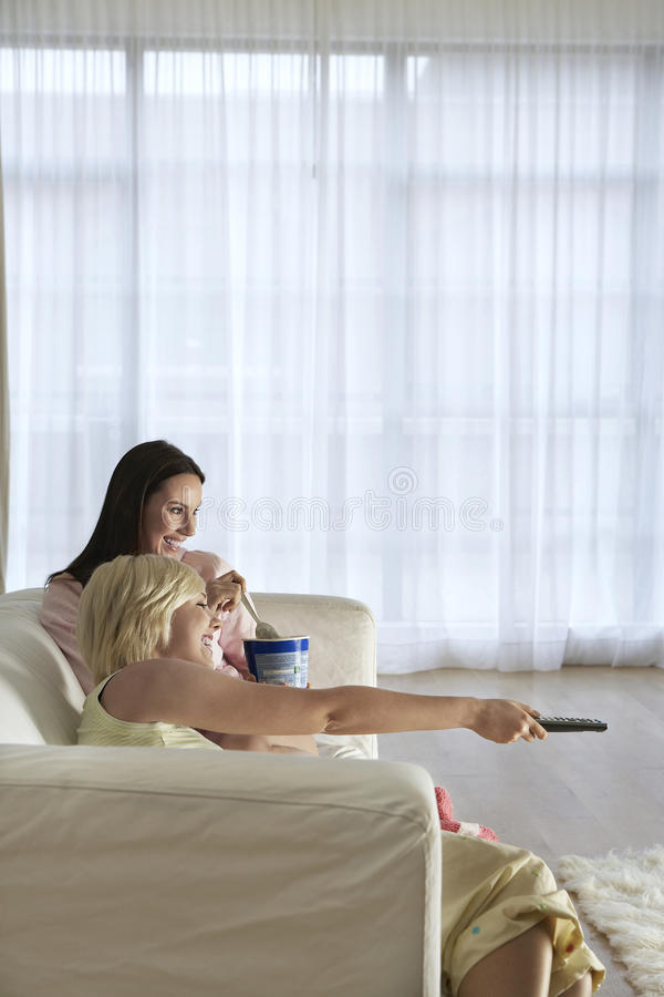 Happy Women Watching TV On Sofa Stock Image