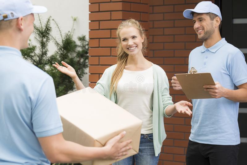 Woman welcoming professional couriers with package and receipt of delivery stock photos