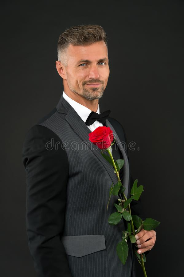 Happy womens day. Elegant man holding red rose on womes day. Handsome man in formal suit and black bowtie celebrating. Womens day. March 8 or international royalty free stock image