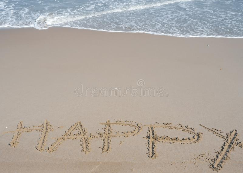 Happy wording written on sand next the sea. relaxing and enjoying summer vacation at the beach.  royalty free stock photography
