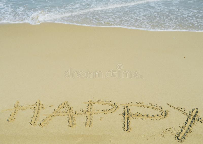 Happy wording written on sand next the sea. relaxing and enjoying summer vacation. At the beach royalty free stock photo