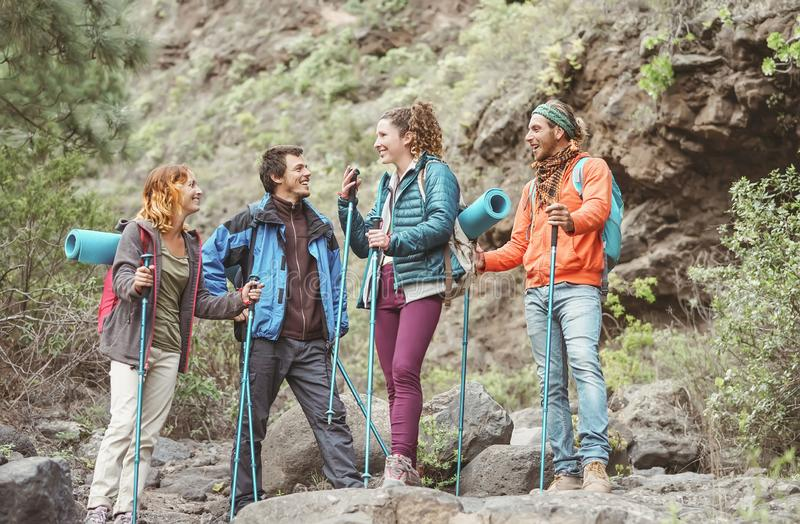 Happy work team friends doing trekking excursion on mountains - Group young tourists hiking and exploring the wild nature royalty free stock photography