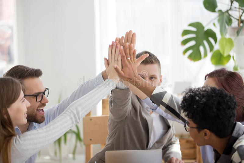 Happy work team giving high five in office at meeting. Happy diverse businesspeople team giving high five sitting in office at boardroom at meeting. Multiracial royalty free stock photography