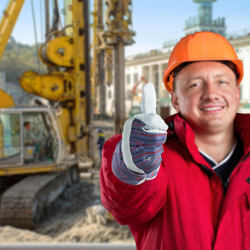 Happy worker. Against construction site stock image