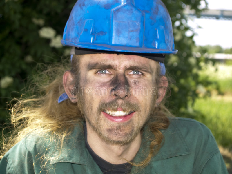 Happy worker. Young happy worker in green uniform and blue helmet stock images