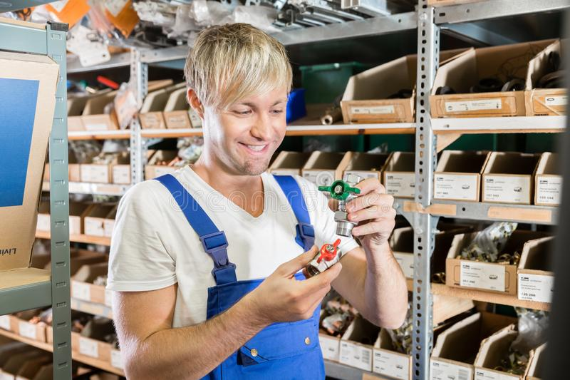 Happy worker comparing two valves in the warehouse of a sanitary shop royalty free stock photography