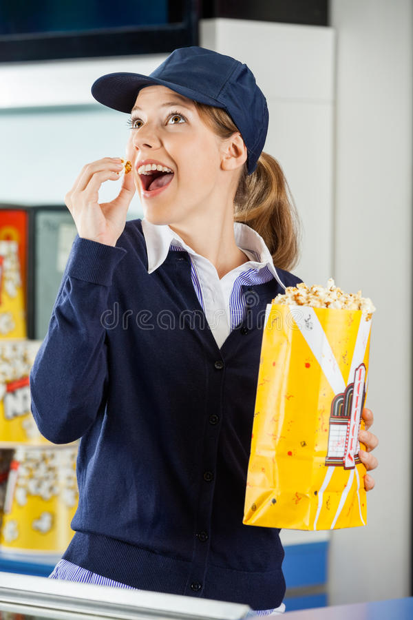 Happy Worker Eating Popcorn At Cinema Concession. Happy female worker looking away while eating popcorn from paperbag at cinema concession stand stock photography
