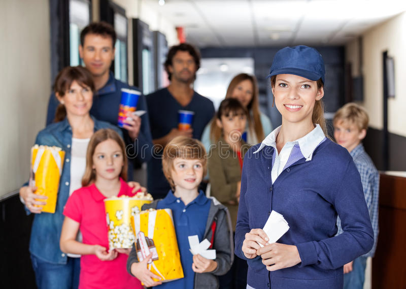 Happy Worker With Families In Background At Cinema. Portrait of happy female worker with families holding snacks in background at cinema royalty free stock images