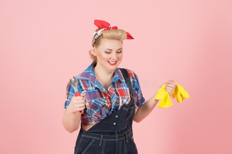 Happy worker girl with wrench and gloves. Teeth smiling woman ready to repair. Pin-up styled blonde girl with instruments royalty free stock image
