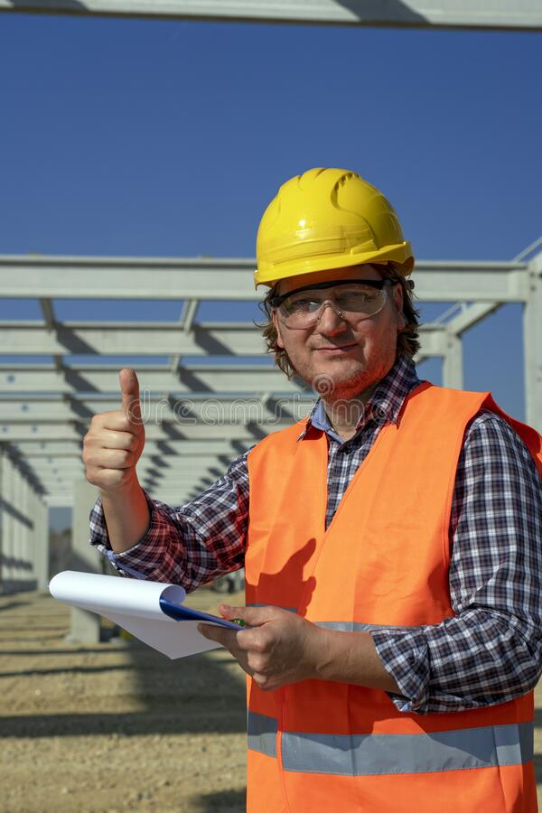 Smiling Construction Worker With Clipboard Giving Thumb Up at a Construction Site royalty free stock photo