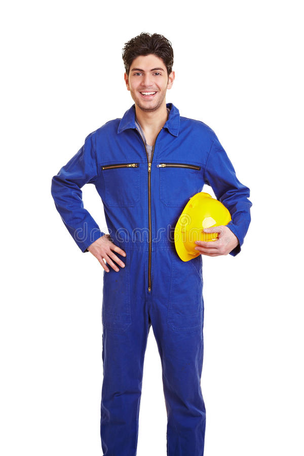 Happy worker in jumpsuit. Young happy construction worker in a blue jumpsuit stock photography