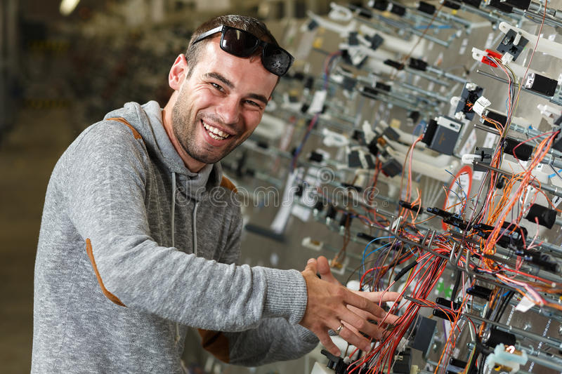 Happy worker. That manufacture the wiring for the car royalty free stock photography