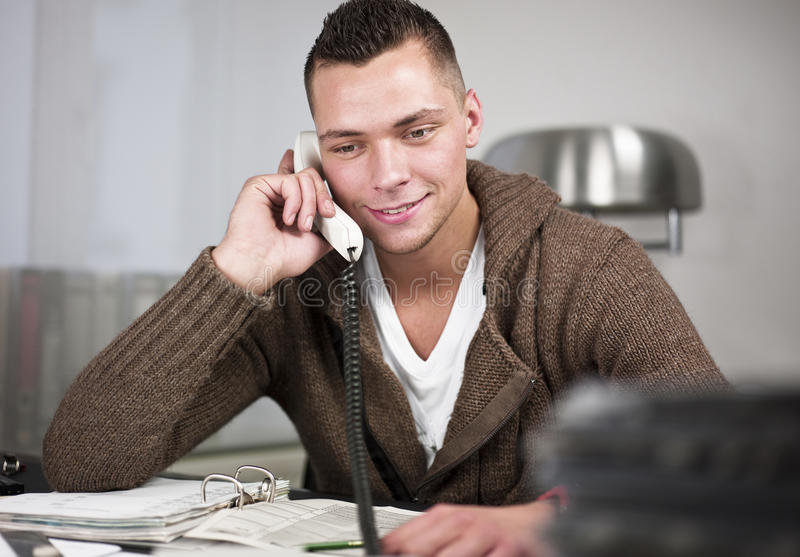 Happy worker in office. Happy young worker in casual clothes using telephone at desk in office stock image