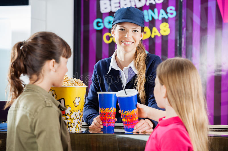 Happy Worker Selling Snacks To Girls At Concession. Portrait of happy female worker selling snacks to girls at cinema concession stand stock photography