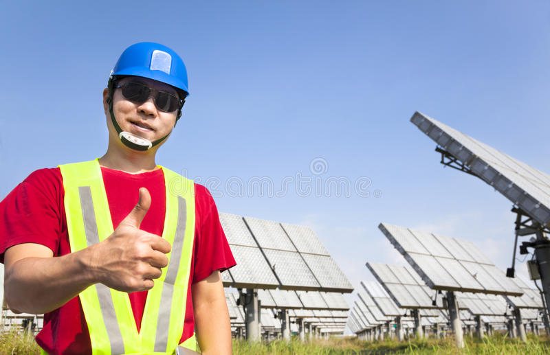 Happy worker with thumb up. And standing before solar panel tracking system stock photo