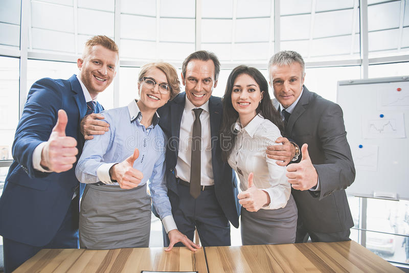 Happy working team is standing at the office royalty free stock photography