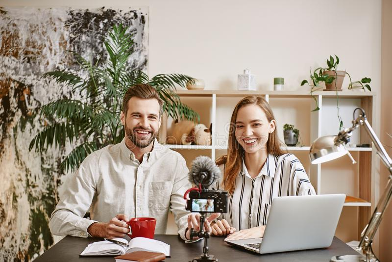 Happy working together. Young couple of bloggers smiling and ready for shooting new vlog stock photo