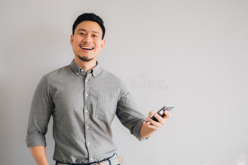 Happy and wow face of Asian man use smartphone on  gray background royalty free stock photography