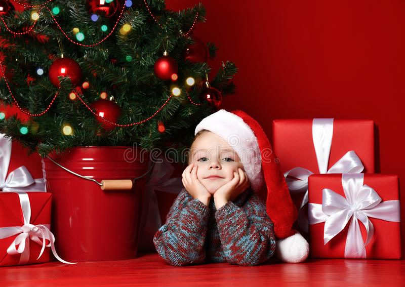 Happy xmas and New Year. Portrait of child in Santa red hat waiting for Christmas gifts. Little baby boy lies under the Christmas tree with presents and is royalty free stock images
