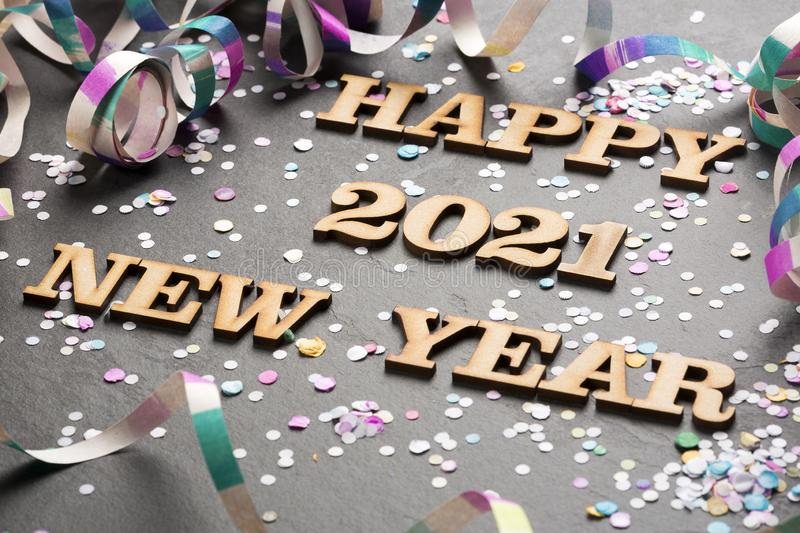 Happy year 2021 - Letters in wood. Black background royalty free stock images