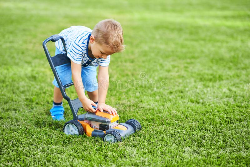 Happy 3 year old boy having fun mowing lawn stock photography