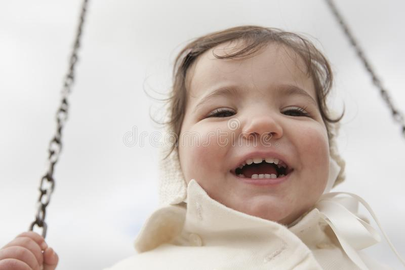 Happy 2 year old girl having fun on a swing on winter. Selective focus royalty free stock photos