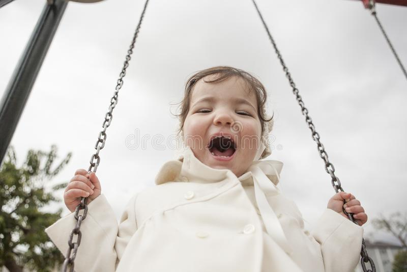Happy 2 year old girl having fun on a swing on winter. Selective focus stock photo
