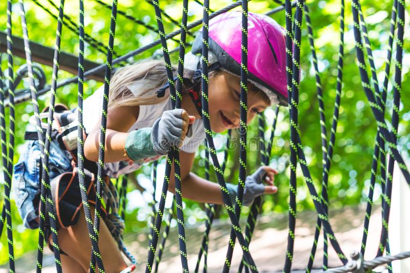 Happy 5 year old girl in pink protective helmet and equipment in a rope park in summer royalty free stock photos