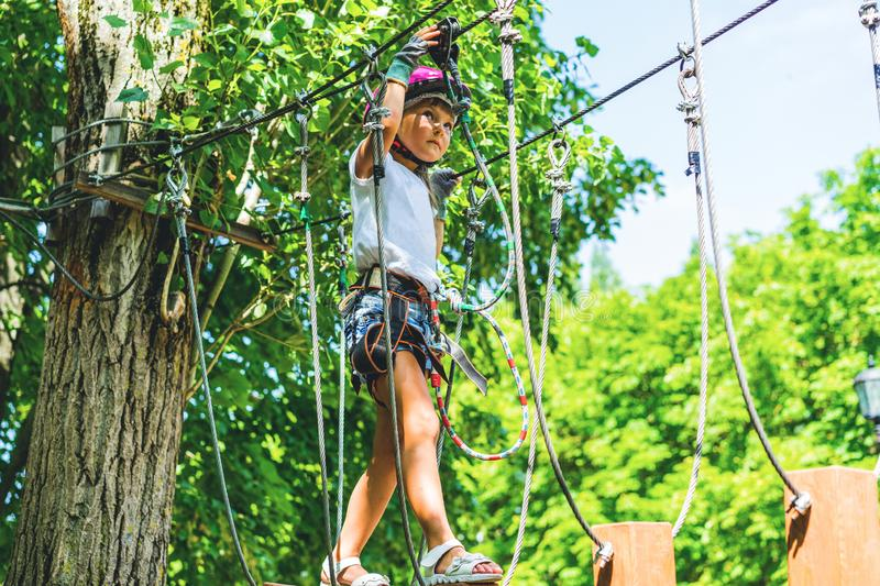 Happy 5 year old girl in pink protective helmet and equipment in a rope park in summer royalty free stock photography