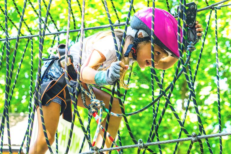 Happy 5 year old girl in pink protective helmet and equipment in a rope park in summer stock photos