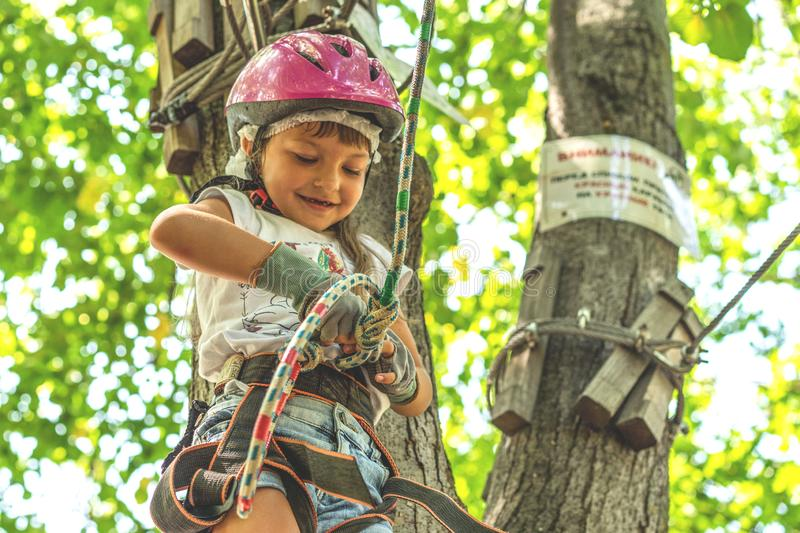 Happy 5 year old girl in pink protective helmet and equipment in a rope park in summer stock images