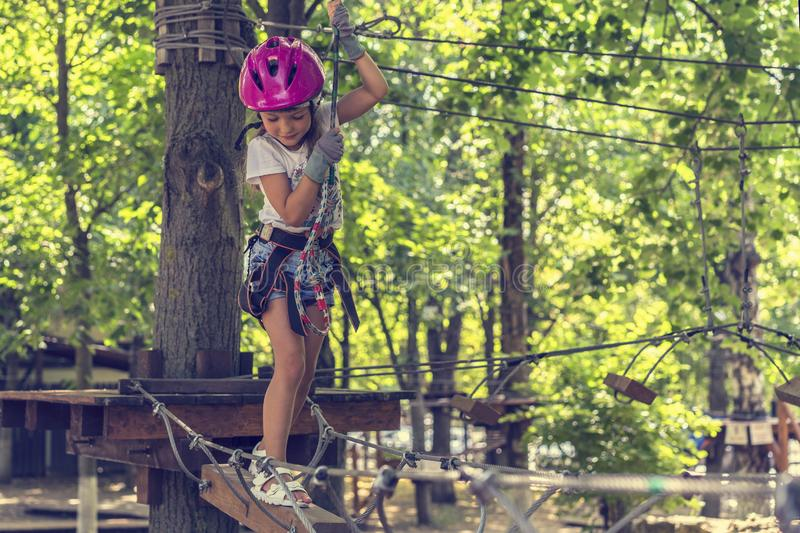 Happy 5 year old girl in pink protective helmet and equipment in a rope park in summer stock photography