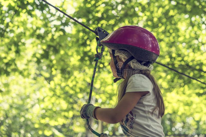 Happy 5 year old girl in pink protective helmet and equipment in a rope park in summer stock image