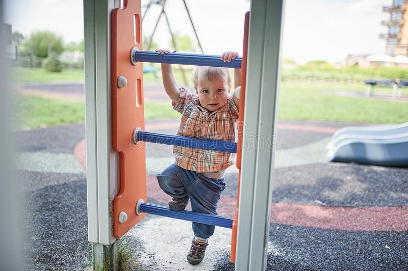 Happy 1 year old toddler climbs on the slide on the playground royalty free stock photography