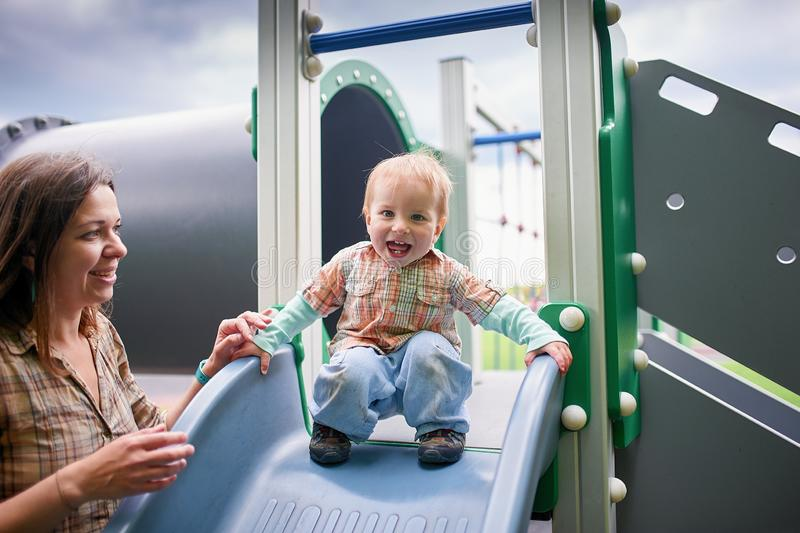 Happy 1 year old toddler playing at the playground with mother royalty free stock photos