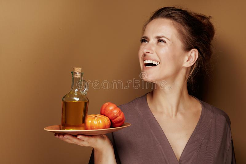 Happy 40 year old woman with pumpkin oil looking at copy space. Hello autumn. happy 40 year old woman in a bathrobe with pumpkin oil looking at copy space on stock photos