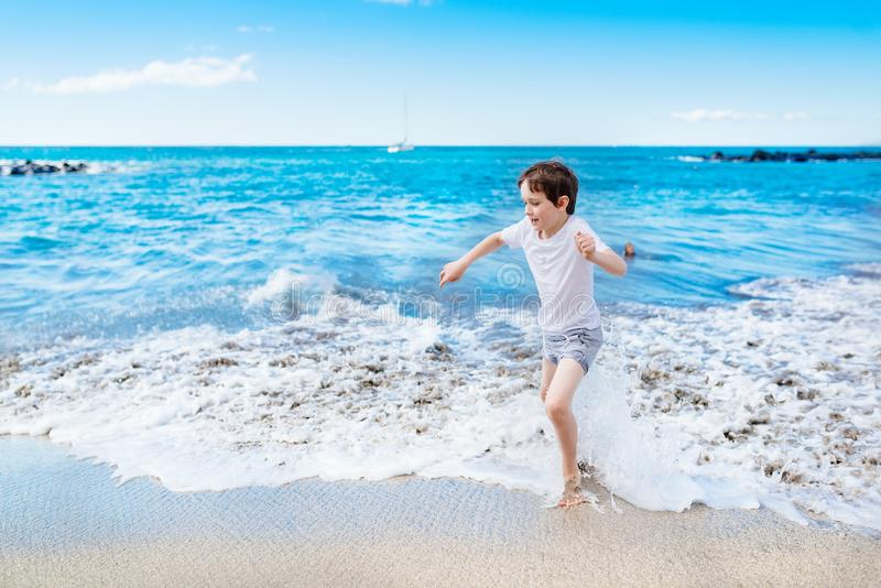 Happy 7 years boy child playing on the beach. Tenerife, Playa del Duque, Costa Adeje royalty free stock photo