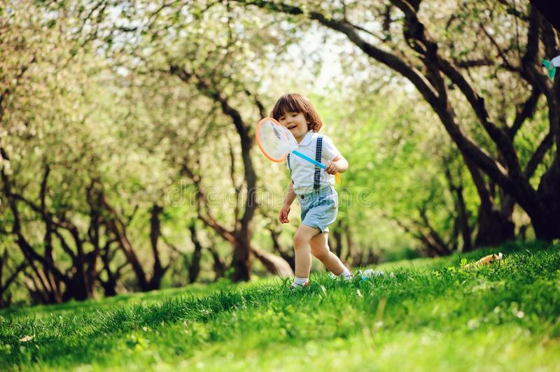 Happy 3 years old child boy catching butterflies with net on the walk in sunny garden or park. Spring and summer outdoor activitie stock photo