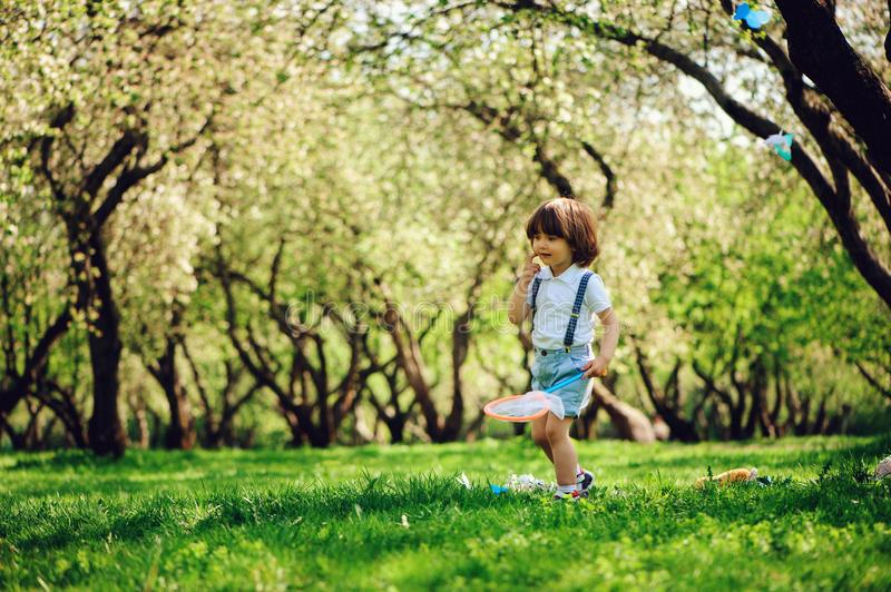 Happy 3 years old child boy catching butterflies with net on the walk in sunny garden or park. Spring and summer outdoor activitie stock photography