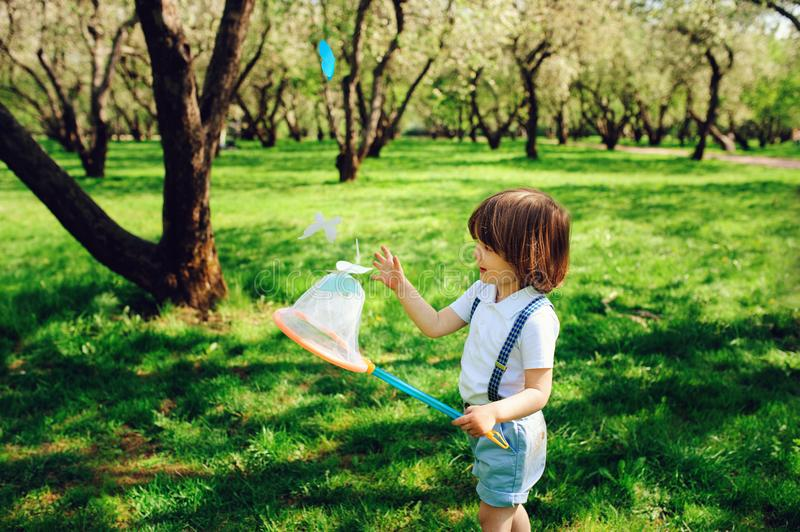 Happy 3 years old child boy catching butterflies with net on the walk in sunny garden or park royalty free stock photo