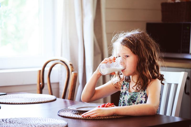 Happy 8 years old child girl having breakfast in country kitchen. Drinking milk and eating toast with strawberry royalty free stock image